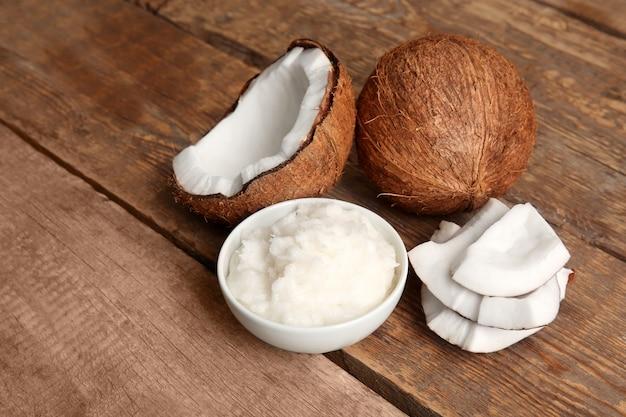 Recipiente con aceite de coco fresco y nuez sobre mesa de madera