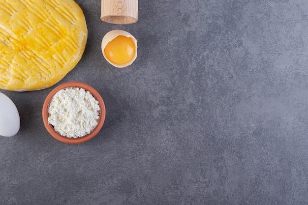 Recipiente de barro lleno de harina con yema de huevo y pan plano colocado sobre el fondo de la mesa de piedra