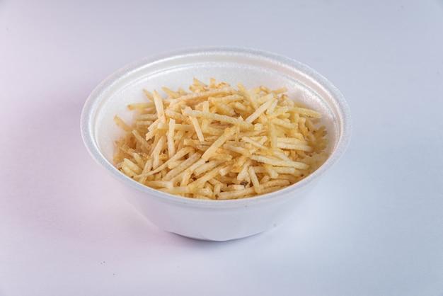 Recipiente blanco con paja de patata sobre fondo blanco.
