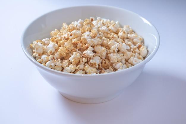 Recipiente blanco con palomitas de maíz dulce sobre fondo blanco.