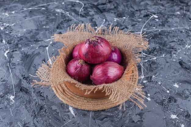 Recipiente de cerámica de cebollas rojas frescas sobre superficie azul