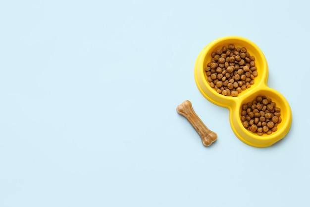 Recipiente con comida para mascotas y masticar hueso sobre fondo de color