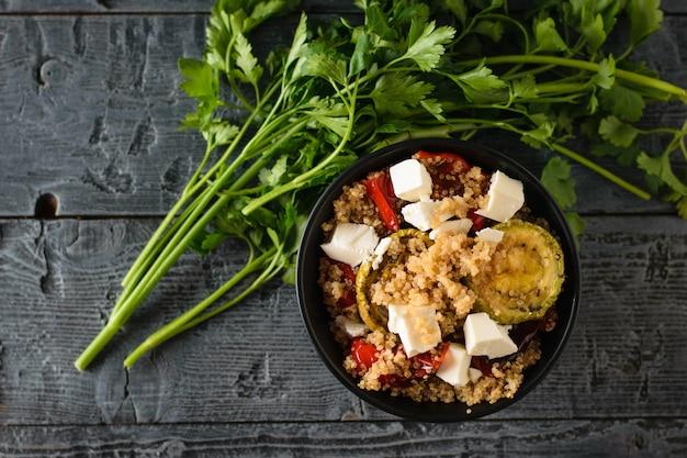 Recipiente con ensalada de queso, quinoa y verduras al horno con un gran manojo de perejil sobre la mesa negra. plato vegetariano. la vista desde arriba. endecha plana.