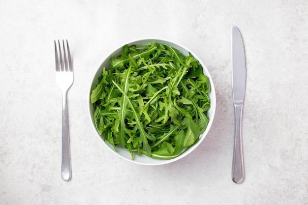 Recipiente con ensalada de rúcula rúcula verde fresca y saludable con cubiertos, tenedor y cuchillo en la superficie gris claro