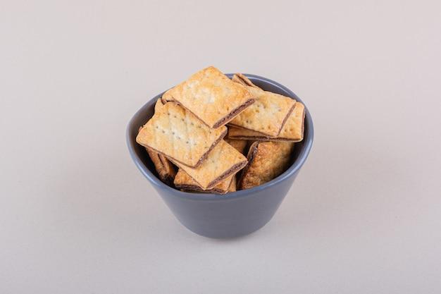 Recipiente hondo con galletas rellenas de chocolate sobre fondo blanco. foto de alta calidad