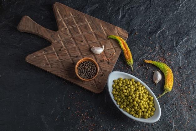 Recipiente lleno de aceitunas verdes y pimientos en el fondo