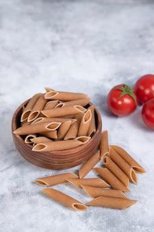 Recipiente de madera lleno de pasta cruda integral penne colocado sobre una mesa de mármol. foto de alta calidad