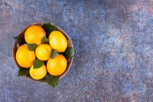 Recipiente de metal lleno de limones frescos con hojas sobre fondo de mármol.