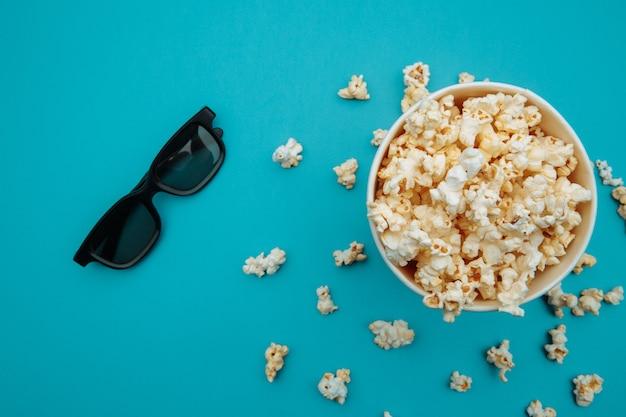 Recipiente con palomitas de maíz y gafas 3d en azul