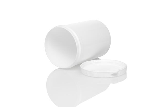 El recipiente de plástico en blanco abierto blanco se encuentra sobre surfase reflactante con tapa blanca cerca.