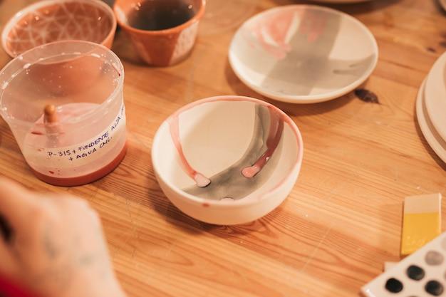 Recipiente y plato de cerámica pintados en mesa de madera