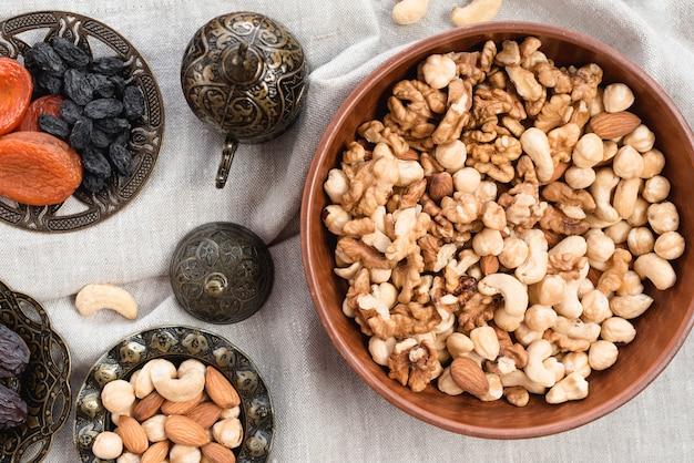 Recipiente redondo de forma grabada con nueces; frutos muertos y bol mezclado de nueces sobre mantel.