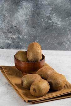 Recipiente con sabrosos kiwis sobre mantel marrón