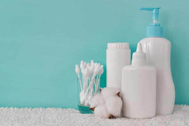 Un recipiente con talco para bebés, una botella de talco, jabón líquido y bastoncillos de algodón en un estante.