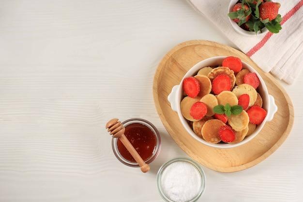 Recipiente con tiny pancake cereal con fresas y hojas de menta sobre un fondo blanco. y placa de madera. comida de moda. mini tortitas de cereales. orientación horizontal, espacio de copia