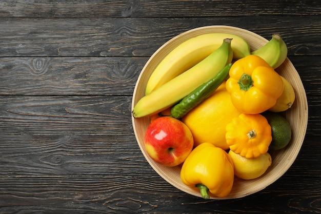 Recipiente con verduras y frutas sobre fondo de madera