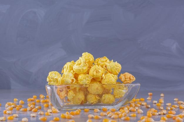 Recipiente de vidrio de deliciosas bolas de maíz en la mesa de piedra