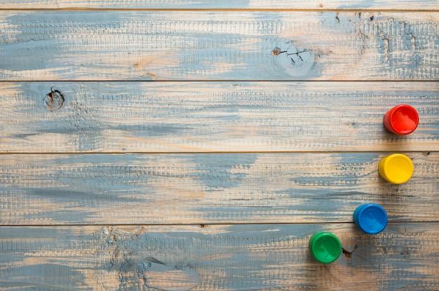 Recipientes de acuarela dispuestos sobre superficie de madera vieja