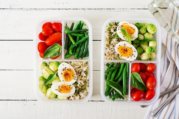Recipientes de comida vegetariana con huevos, coles de brussel, judías verdes y tomate.