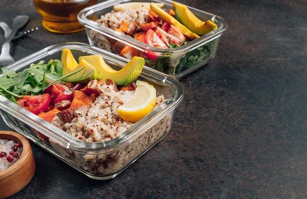 Recipientes de preparación de comidas saludables vegetarianas. verduras crudas y quinua para el almuerzo en mesa oscura.