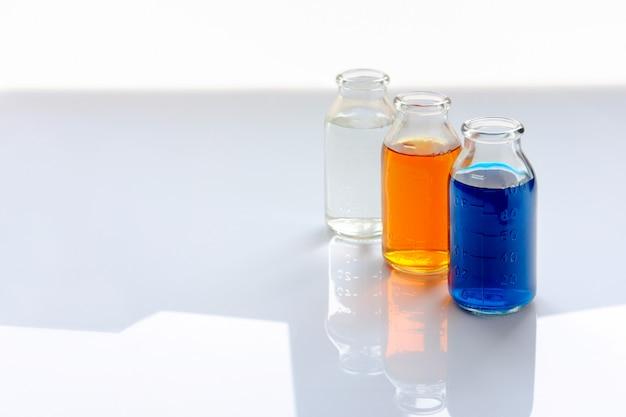 Recipientes químicos con líquidos coloridos sobre fondo blanco.