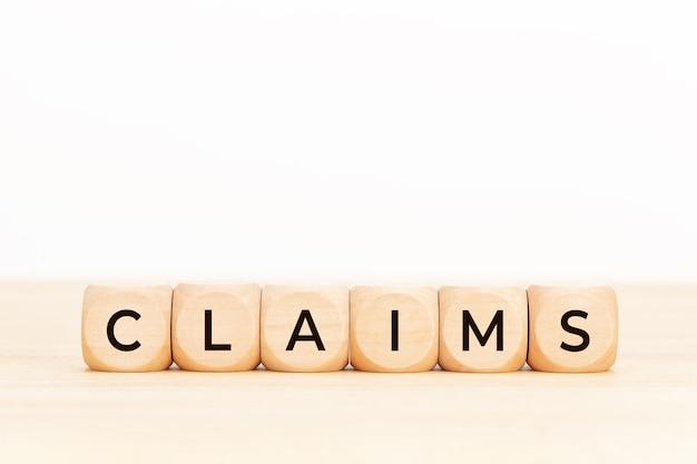 Reclamaciones palabra en forma de bloque de madera espacio de copia fondo blanco