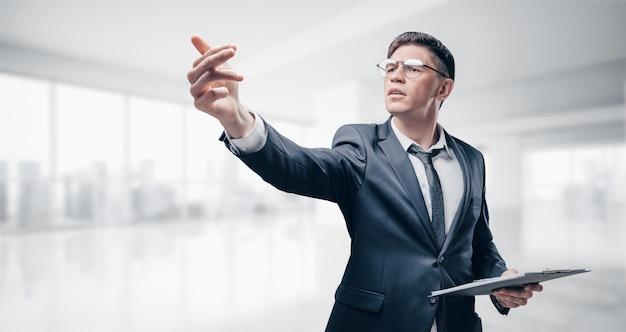 Reclutador en traje de negocios está de pie en la oficina con una lista en sus manos. concepto de contratación.