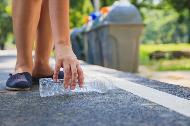 Recoge botellas de plástico en la carretera.