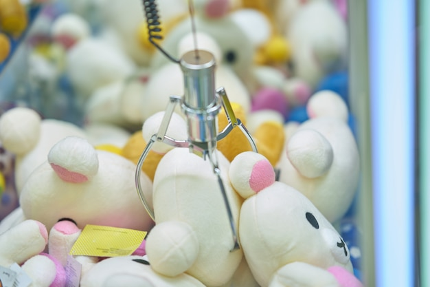 Recogedor de muñecas o máquina de pinza de garra en un juego de arcade, muñeca de sujeción