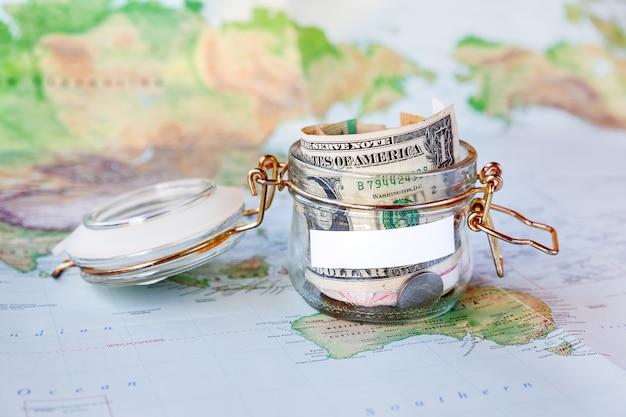 Recoger dinero para viajar. lata de vidrio como hucha con ahorros en efectivo (billetes y monedas) en el mapa
