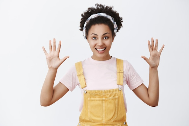 Recogí una docena. retrato de mujer joven encantadora, amable y de aspecto amistoso con piel oscura, con diadema y un mono de moda amarillo, levantando las palmas y mostrando el número diez, sonriendo ampliamente