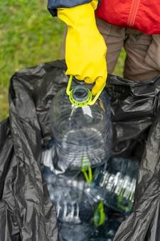 Recogida selectiva de basura. poner a mano la botella de plástico en una bolsa de plástico negra llena de otras botellas.