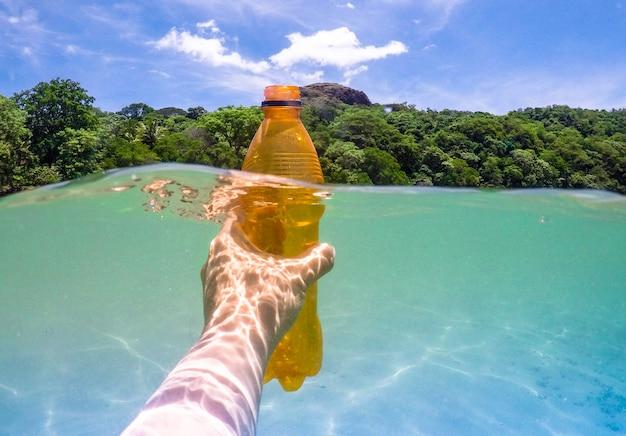 Recogiendo una botella de plástico del ocwan, recicla