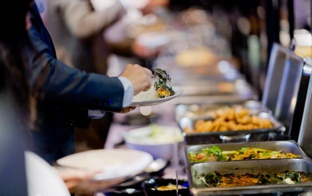 Recogiendo la comida, comida buffet en el restaurante, catering