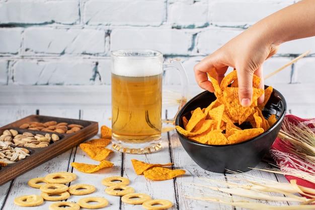 Recogiendo papas fritas del tazón en una mesa de cerveza