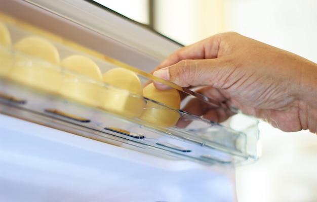 Recoja el huevo de gallina del refrigerador, los huevos en el estante del refrigerador