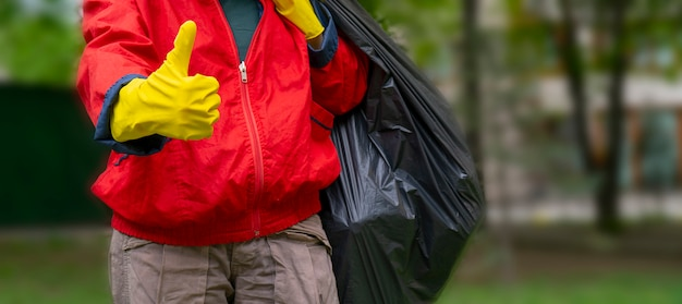 Recolección de basura. hombre con abrigo rojo y guantes amarillos que muestran el pulgar hacia arriba, lleva una gran bolsa negra con basura.