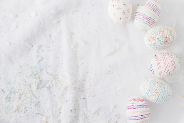 Recolección de huevos de pascua con dibujos cerca de plumas en textil