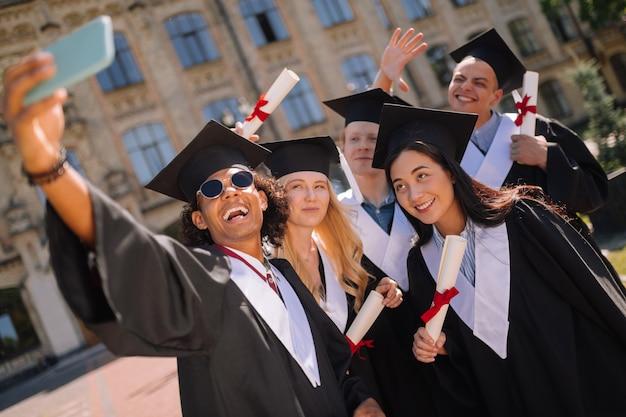 Recordando el momento. graduados felices con sus diplomas de pie juntos cerca de su universidad y tomando un selfie.