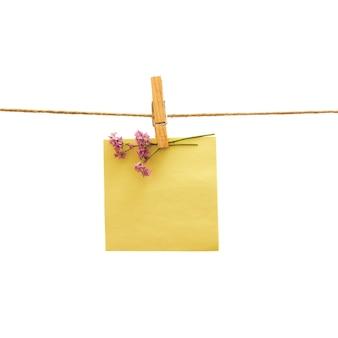 Recordatorio amarillo y flor violeta con pinza de ropa sobre blanco