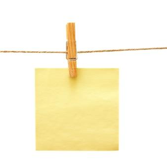 Recordatorio amarillo con pinza de ropa sobre blanco
