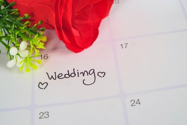 Recordatorio del día de la boda en la planificación de calendario con rosa roja.