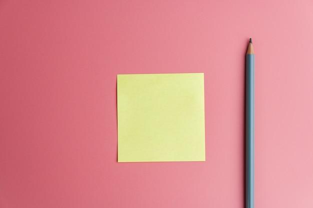 Un recordatorio de nota adhesiva amarilla y un lápiz sobre un rojo