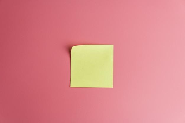 Un recordatorio de nota adhesiva amarilla sobre rojo