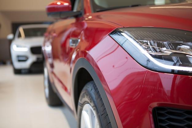 Recorta cerca de un automóvil nuevo y moderno a la venta en el salón del concesionario local. concepto de venta de coches