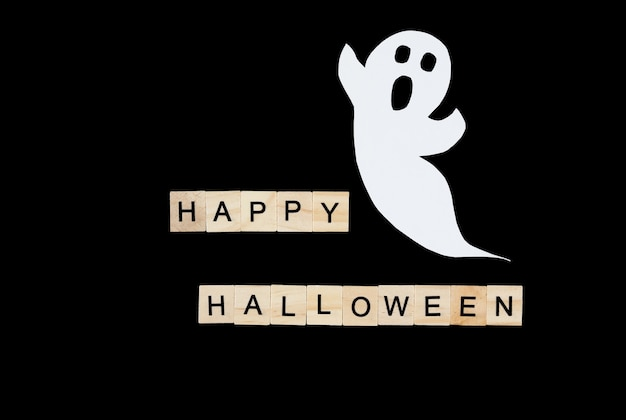 Recorta el fantasma de papel y las letras de madera feliz halloween en negro.