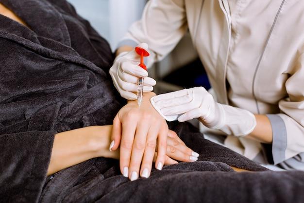 Recorta la imagen de una mujer que recibe inyecciones de relleno rejuvenecedoras en la mano. esteticista femenina inyectando relleno en la piel de la mano de un cliente