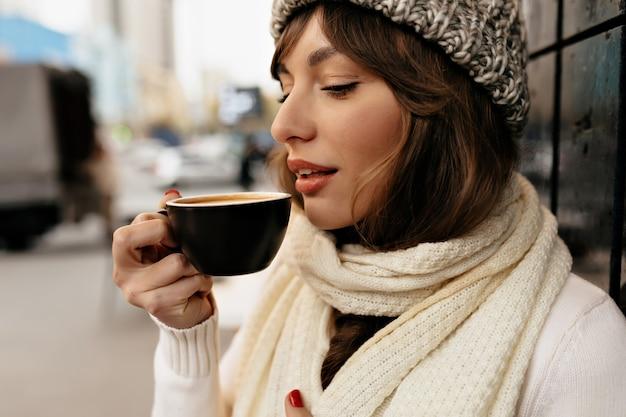 Recorta el retrato exterior de una linda chica encantadora con gorro de punto y bufanda bebiendo café y disfrutando de una pausa para el café