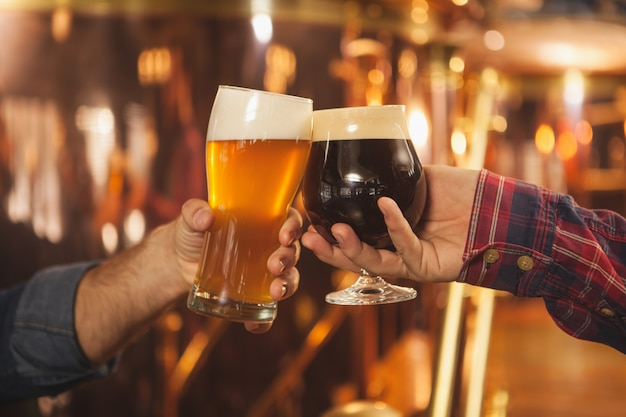 Recortada cerca de dos hombres tintineando vasos de cerveza juntos, celebrando en el pub de cerveza