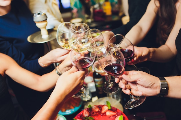 Recortada cerca foto de copas con champán. los jóvenes están brindando para celebrar el evento. la mesa está llena de sabrosas comidas y bebidas.